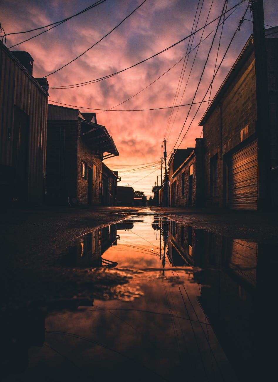 water puddle between buildings during golden hour