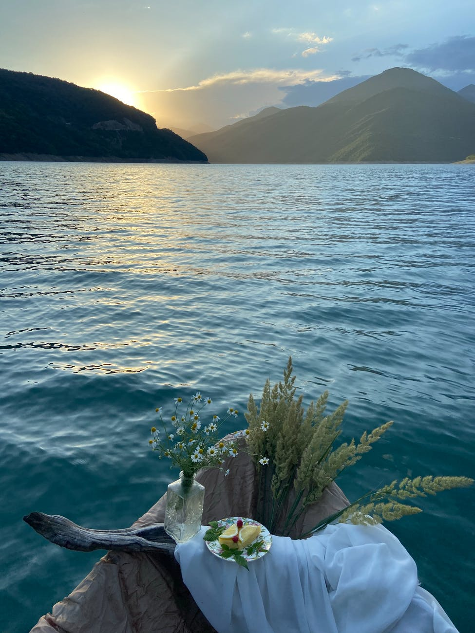 boat with vase of flowers and dried grass on lake
