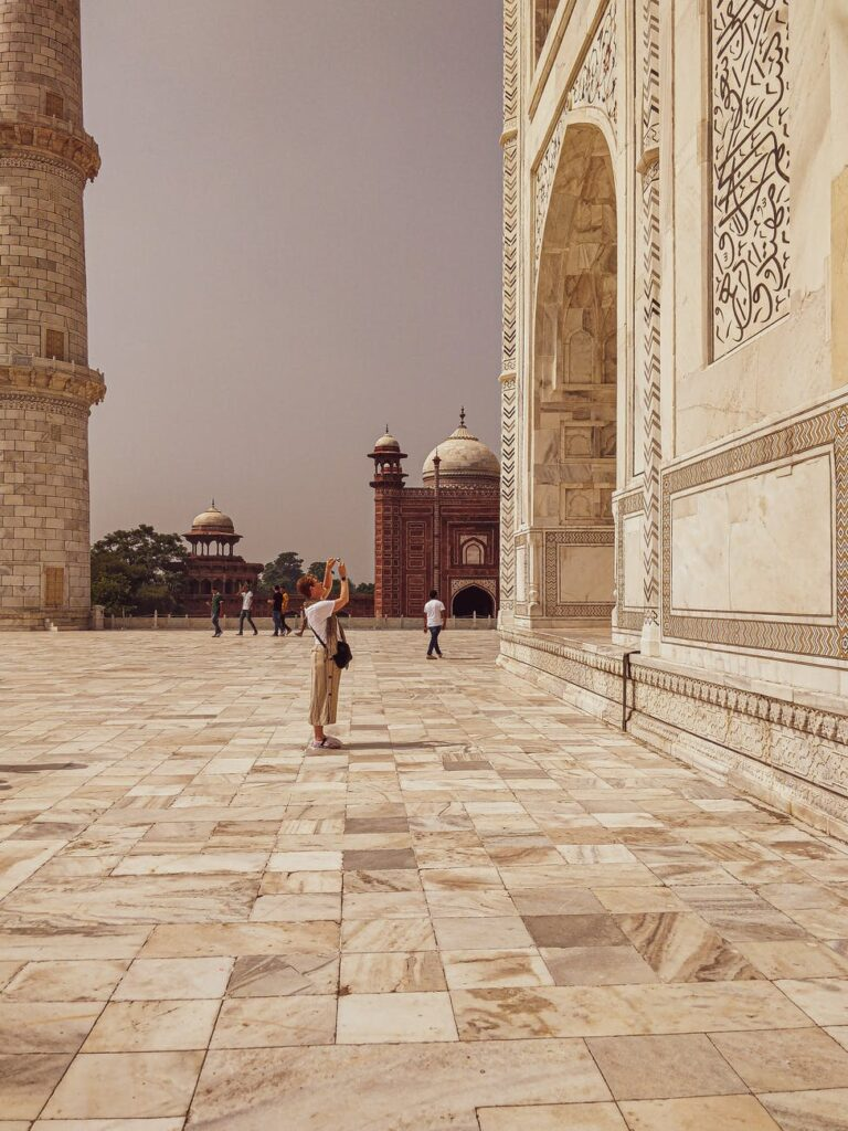 exterior of taj mahal in india with tourists walking around