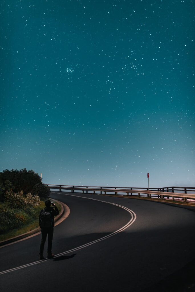 anonymous tourist taking photo of starry sky while standing on road