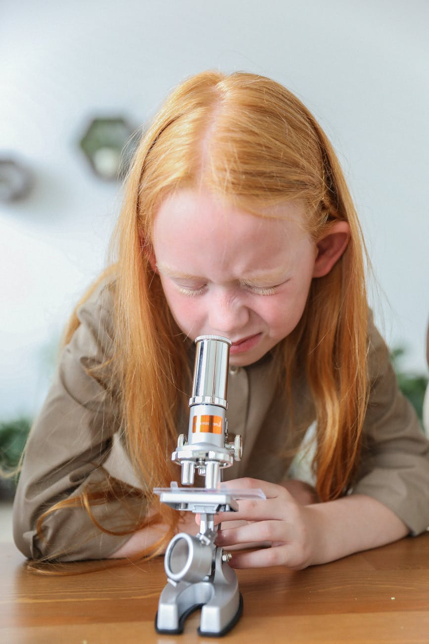 concentrated kid using microscope in science class