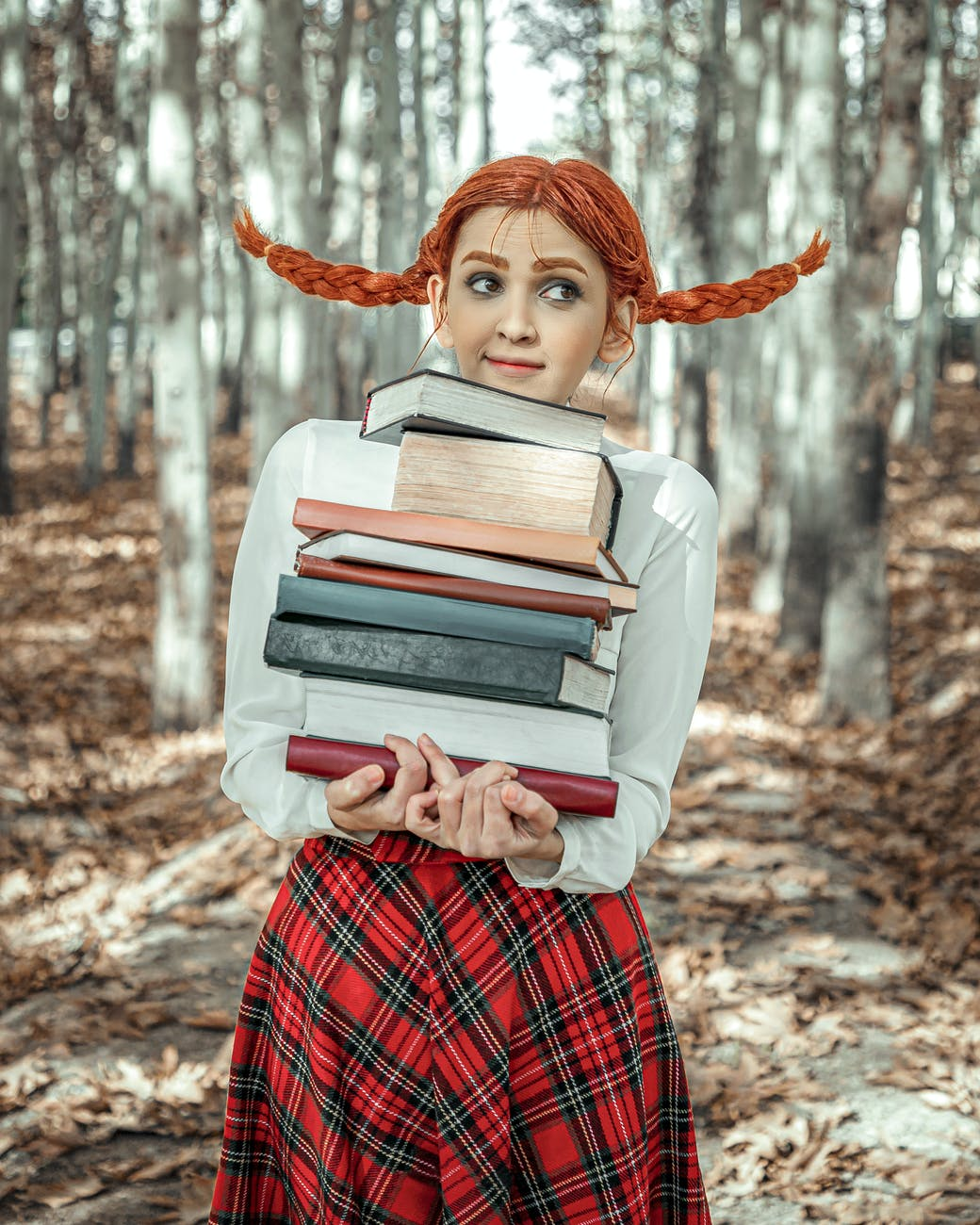 woman in red and white plaid dress shirt holding books