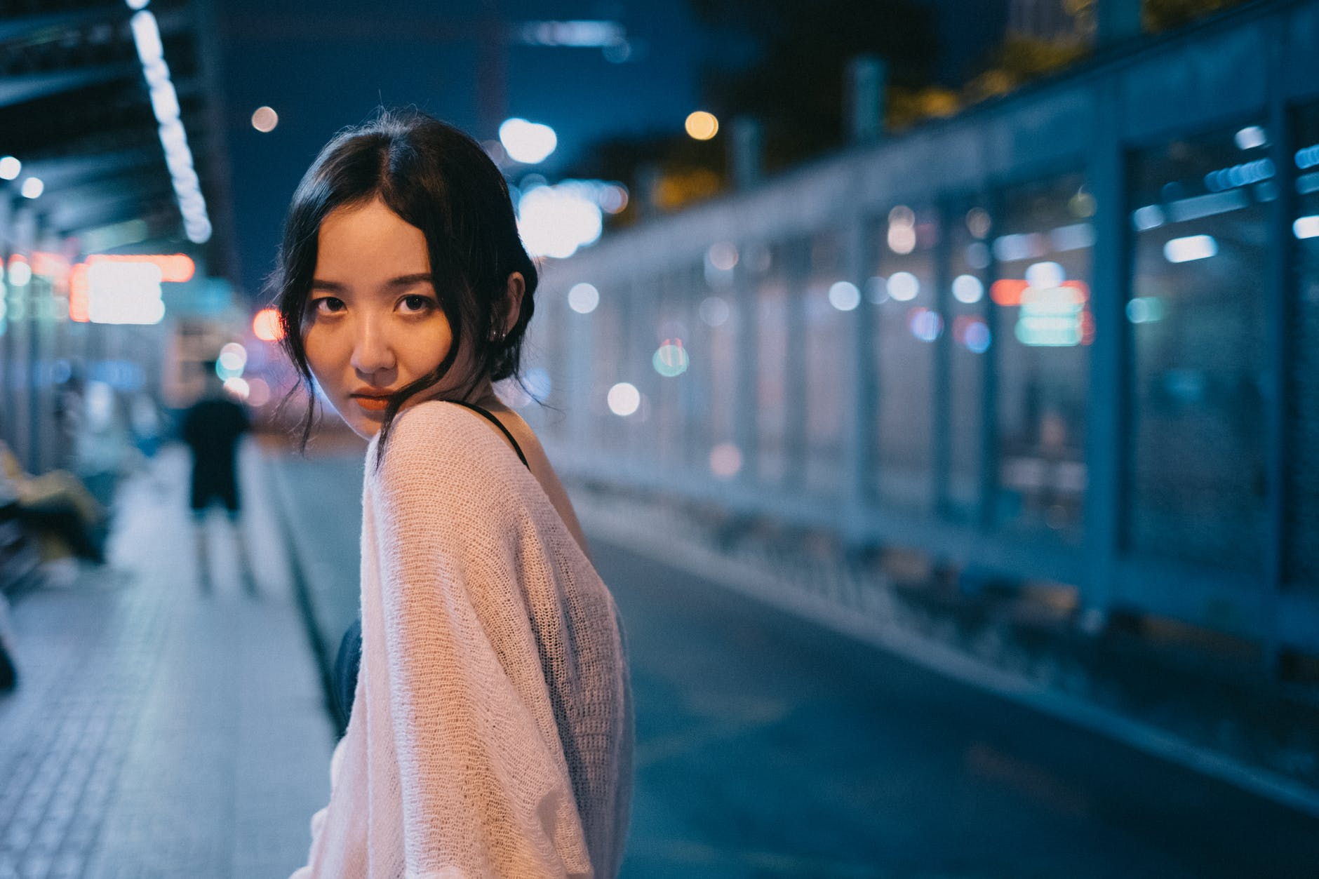 young asian woman in evening street with bright lights