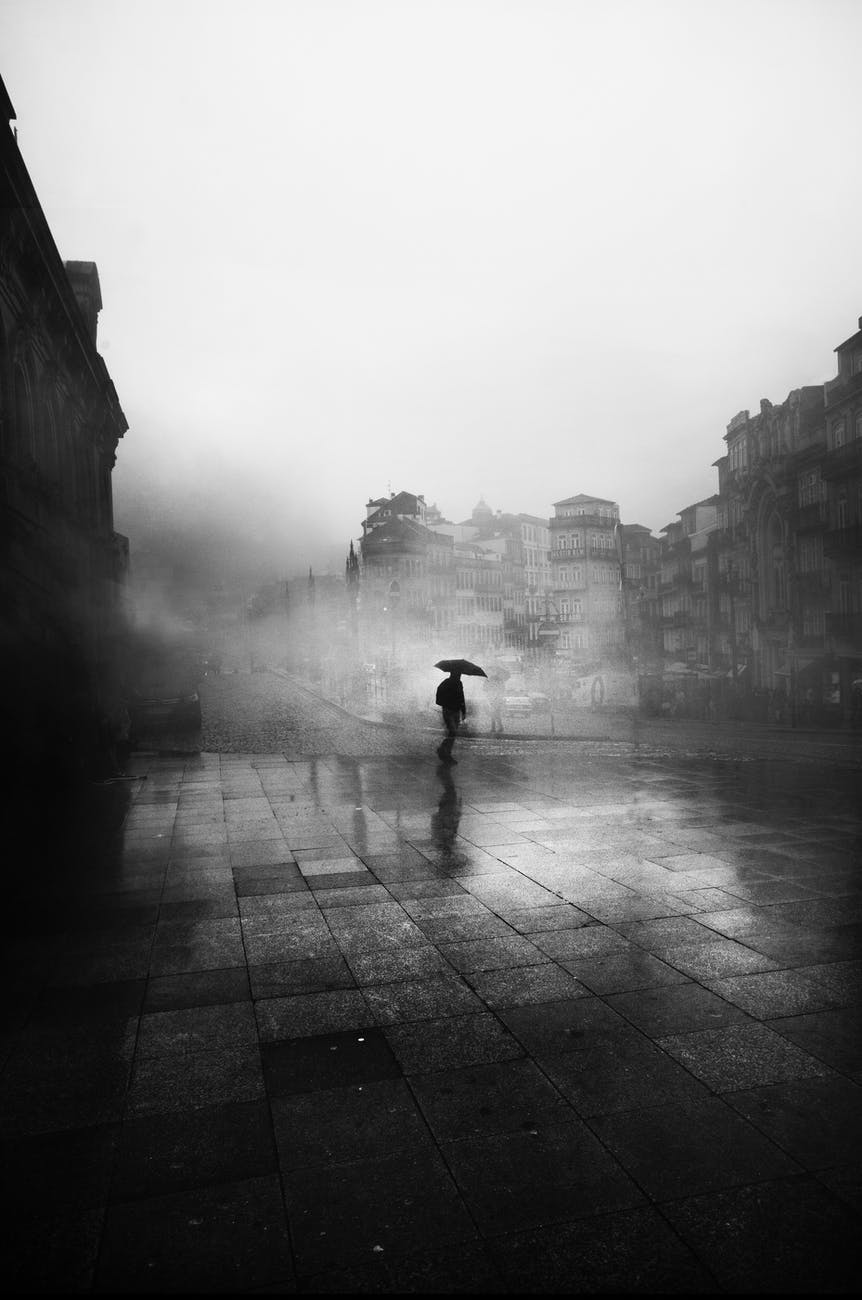 black and white photo of man with umbrella