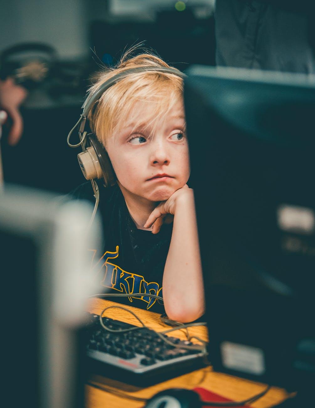 photo of boy wearing headphone